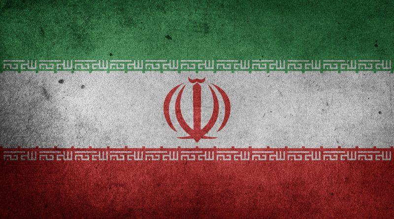 Obraz przedstawia flagę państwową Iranu. Trzy pasy od góry patrząc zielony biały czerwony. Na białym pasie herb Iranu