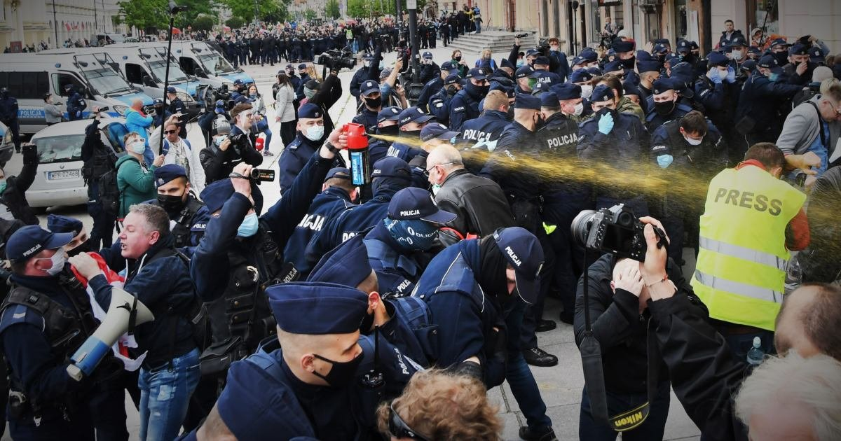 Policjant spełniajacy dwie funkcje jednocześnie. Funkionariszu dokumentuje całoś zająca na kamerze jednocześnie używając reczny miotacz gazu nad głowami swoich kolegów.