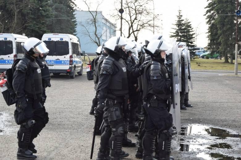 Modelowa formacja podczas ćwiczeń OPP Rzeszów. Widzimy rząd tarcz, za nim funcionariuszy z pałkami bez tarcz, którrzy będą podejmowac aresztowania oraz z tyły dwuch policjnatów z plecakowymi miotaczami gazu (czerwoone butle na lecach), a pomiędzy nimi dowódcę oddziału